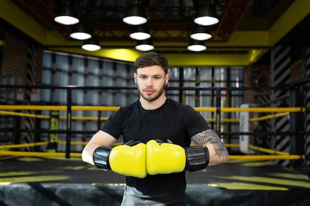 Een jonge atleet in gele bokshandschoenen