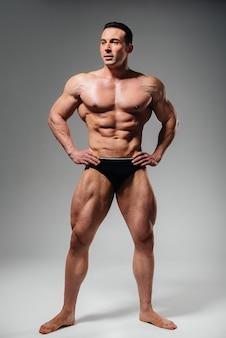 Een jonge atleetbodybuilder poseert topless in de studio en pronkt met zijn buikspieren en spieren