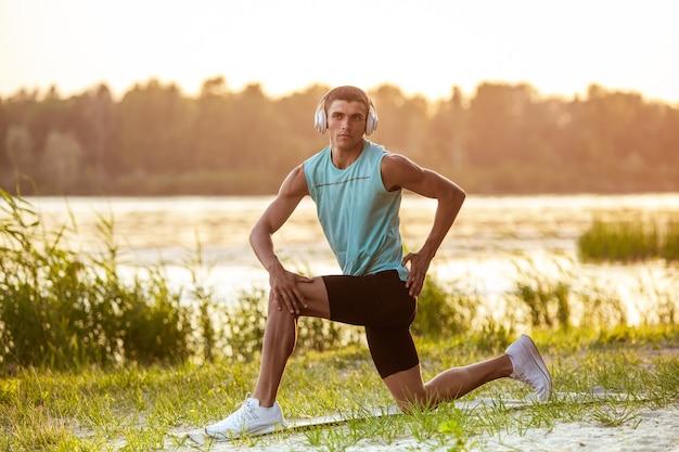 Een jonge atletische man die aan het trainen is en buiten aan de rivier naar de muziek luistert