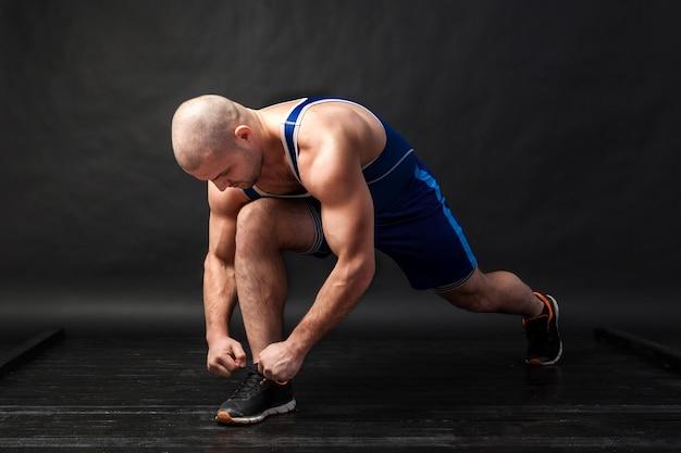 Een jonge atletische man in blauwe worstelen lastige en blauwe korte broek bindt schoenveters op sneakers op een zwarte geïsoleerde achtergrond in een fotostudio