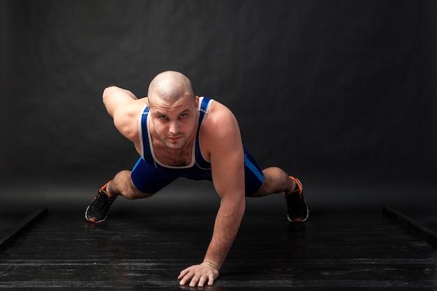Een jonge atletische man in blauwe worstelen lastige en blauwe korte broek doet push-ups op een zwartharige geïsoleerde achtergrond in een fotostudio