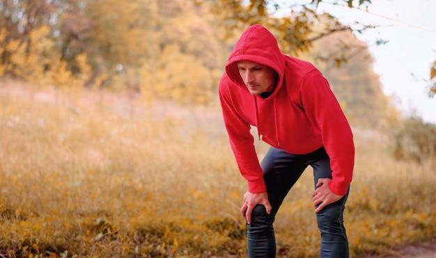 Een jonge atletische man in een rood sportjack met capuchon en zwarte sportleggings die na het joggen in het kleurrijke gele herfstbos rusten.