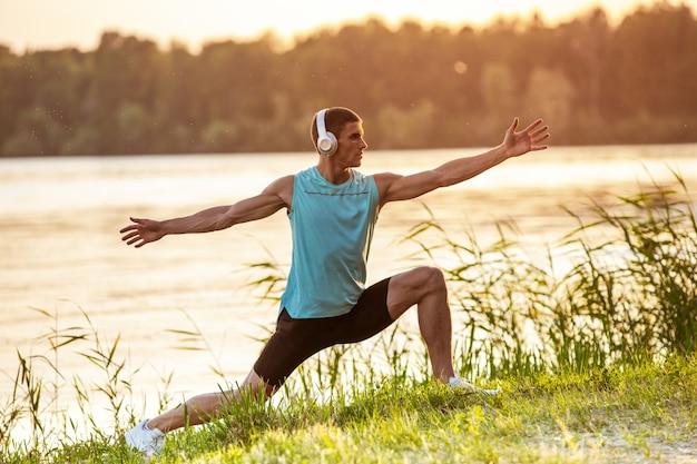 Een jonge atletische man traint het luisteren naar de muziek aan de rivier buiten