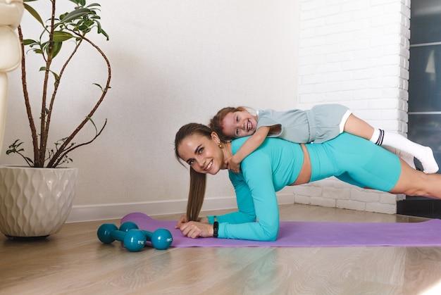 Een jonge atletische moeder en een meisje doen thuis samen oefeningen