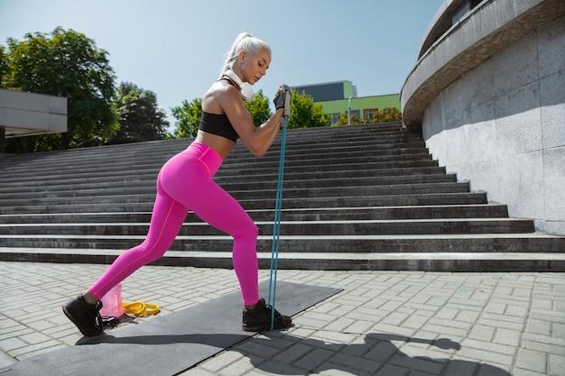 Een jonge atletische vrouw die aan het trainen is in de straat van de stad