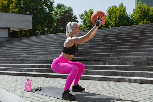 Een jonge atletische vrouw in overhemd en witte hoofdtelefoons die aan de muziek in de straat buiten werken luisteren. squats doen met de bal. concept van een gezonde levensstijl, sport, activiteit, gewichtsverlies.