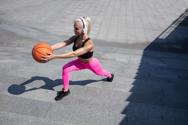 Een jonge atletische vrouw in overhemd en witte hoofdtelefoons die aan de muziek in de straat buiten werken uitwerken. lunges doen met de bal. concept van een gezonde levensstijl, sport, activiteit, gewichtsverlies.
