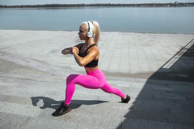Een jonge atletische vrouw in overhemd en witte hoofdtelefoons die aan de muziek in de straat buiten werken uitwerken. lunges doen op een zonnige dag. concept van een gezonde levensstijl, sport, activiteit, gewichtsverlies.