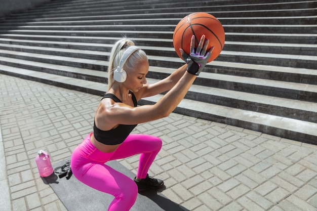 Een jonge atletische vrouw in overhemd en witte hoofdtelefoons die aan de muziek in de straat buiten werken uitwerken. squats doen met de bal. concept van een gezonde levensstijl, sport, activiteit, gewichtsverlies.