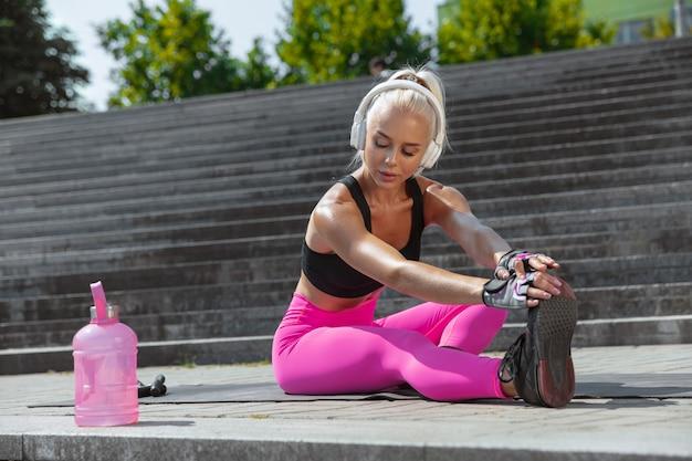 Een jonge atletische vrouw in overhemd en witte hoofdtelefoons die aan de muziek in de straat buiten werken uitwerken