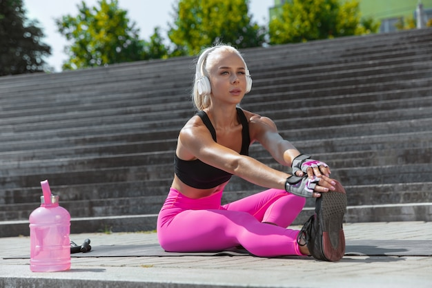 Een jonge atletische vrouw in overhemd en witte hoofdtelefoons die aan de muziek in de straat buiten werken uitwerken.