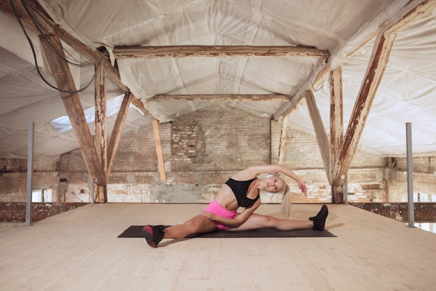 Een jonge atletische vrouw in overhemd en witte hoofdtelefoons die aan de muziek op een verlaten bouwplaats uitwerken. rekken. concept van een gezonde levensstijl, sport, activiteit, gewichtsverlies.