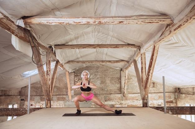 Een jonge atletische vrouw in overhemd en witte hoofdtelefoons die aan de muziek op een verlaten bouwplaats uitwerken. squats maken. concept van een gezonde levensstijl, sport, activiteit, gewichtsverlies.