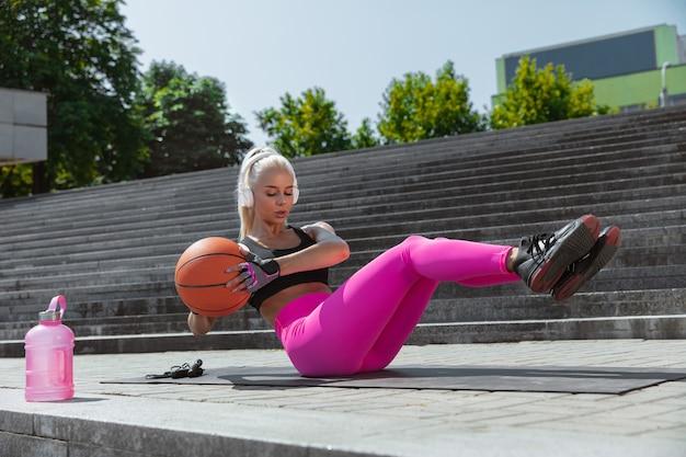 Een jonge atletische vrouw in witte hoofdtelefoons opleiding