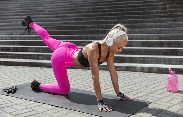 Een jonge atletische vrouw in witte koptelefoon training, luisteren naar de muziek op straat buitenshuis.