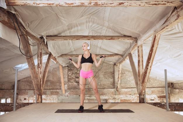 Een jonge atletische vrouw in witte koptelefoon traint het luisteren naar de muziek op een verlaten bouwplaats. met het springtouw. concept van een gezonde levensstijl, sport, activiteit, gewichtsverlies.