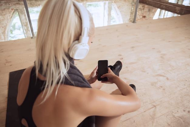 Een jonge atletische vrouw in witte koptelefoon traint het luisteren naar de muziek op een verlaten bouwplaats