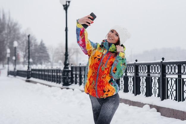 Een jonge atletische vrouw maakt een selfie op een ijzige en besneeuwde dag. fitness, recreatie