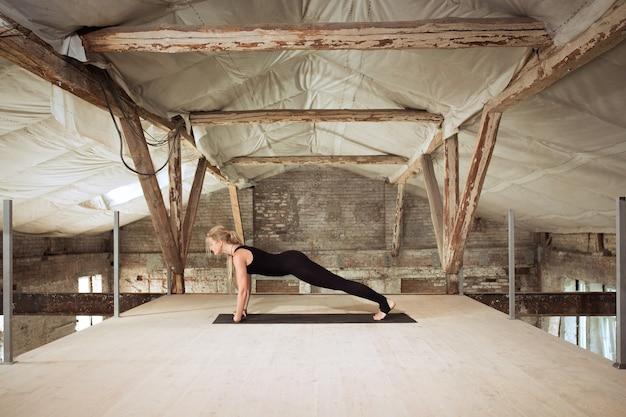 Een jonge atletische vrouw oefent yoga op een verlaten bouwgebouw. geestelijke en lichamelijke gezondheid. concept van een gezonde levensstijl, sport, activiteit, gewichtsverlies, concentratie.