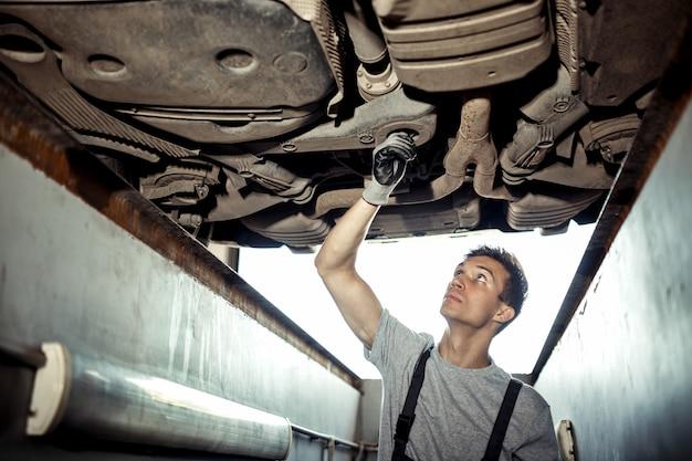 Een jonge automonteur controleert de details van een voertuig.