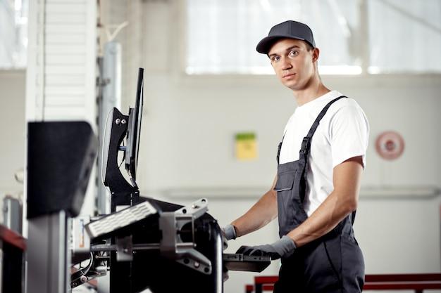 Een jonge automonteur in uniform is een check-in computer die op zoek is naar bugs in een automotor.