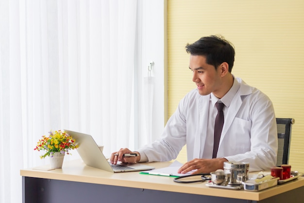 Een jonge aziatische arts glimlacht en werkt aan het ziekenhuisbureau.