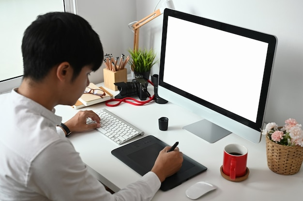 Een jonge aziatische grafisch ontwerper werkt op zijn werkplek aan een grafisch tablet