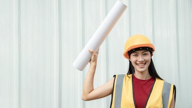Een jonge aziatische ingenieur houdt een bord met een wit bord voor het schrijven van berichten of aankondigingen tegen een achtergrond van metalen plaat op de bouwplaats. leider concept.