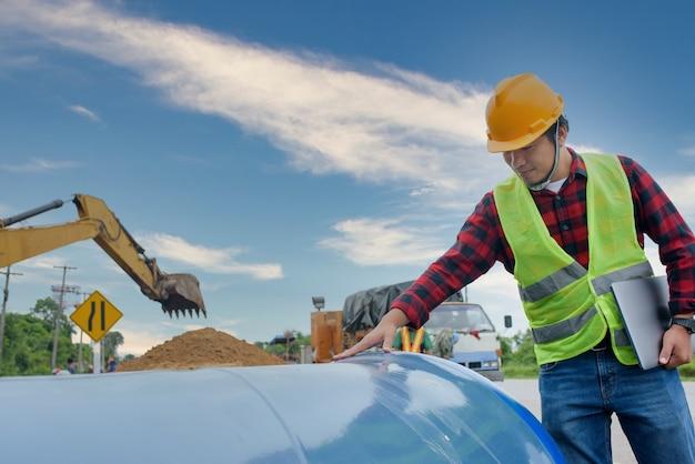 Een jonge aziatische ingenieur inspecteert een groot riool op de bouwplaats