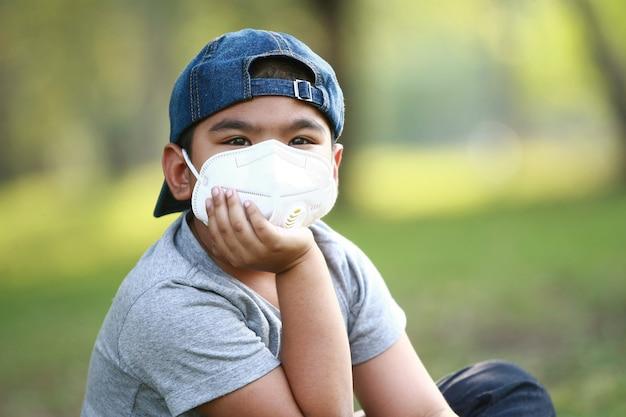Een jonge aziatische jongen, 7 jaar oud, draagt een masker ter bescherming tegen stof pm 2,5 en ziektekiemen