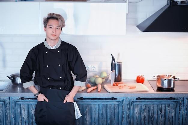 Een jonge aziatische kok in de keuken bereidt eten in een kokskostuum