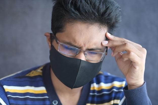Een jonge aziatische man met een beschermend masker in het gezicht voelt zich verdrietig
