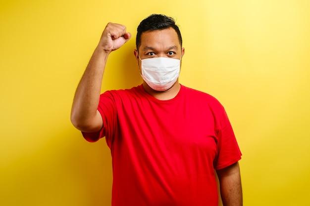 Een jonge aziatische man met een medisch gezichtsmasker dat beschermt tegen de verspreiding van corona virusziekte. close-up van een man met een chirurgisch masker op zijn gezicht tegen een gele achtergrond