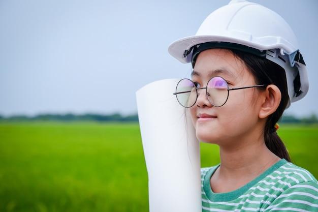 Een jonge aziatische meisjesingenieur die een witte veiligheidshoed draagt die een document broodje houdt.