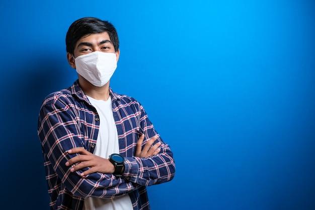 Een jonge aziatische student die een medisch gezichtsmasker draagt dat beschermt tegen de verspreiding van corona-virusziekte. close-up van een man met een chirurgisch masker op zijn gezicht tegen een blauwe achtergrond