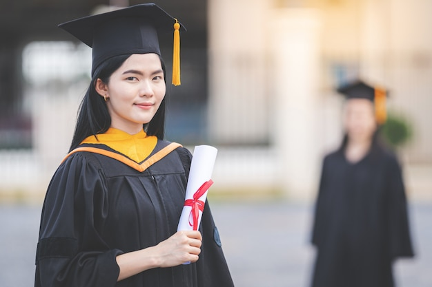 Een jonge aziatische vrouw afgestudeerd aan de universiteit in afstudeerjurk en baret heeft een diploma staat voor het universiteitsgebouw na deelname aan het begin van de universiteit