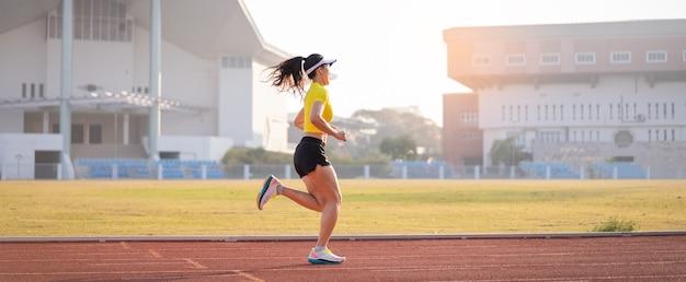 Een jonge aziatische vrouw atleet runner joggen op de atletiekbaan in het stadsstadion in de zonnige ochtend om fitness en een gezonde levensstijl te behouden. jonge fitness vrouw loopt op stadion track. sport en recreatie