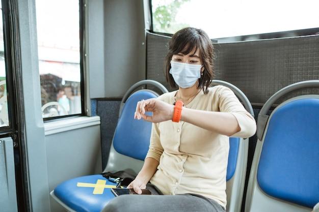 Een jonge aziatische vrouw die een masker draagt, zit op een bank tijdens het reizen naar haar horloge in de bus te kijken