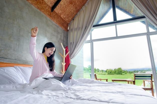 Een jonge aziatische vrouw is blij en verfrist in haar bed.