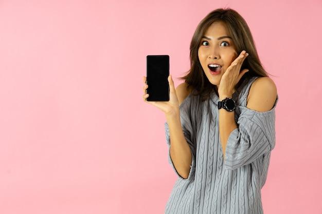 Een jonge aziatische vrouw leek verrast door een promotie op het scherm van een smartphone