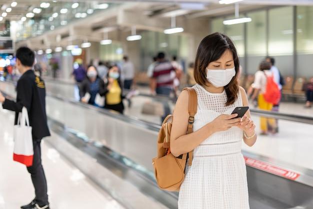 Een jonge aziatische vrouw met een masker op de luchthaven is op weg naar het vliegtuig bij de gate. reizen tijdens de covit-19-epidemie