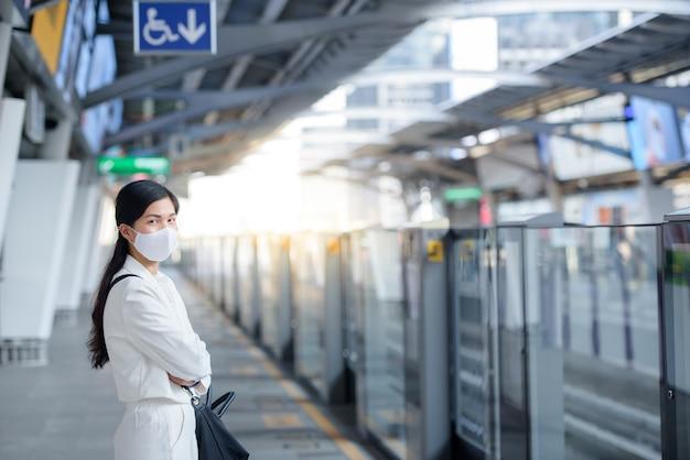 Een jonge aziatische vrouw met een masker tegen het nieuwe coronavirus (covid-19) loopt in een menigte op een openbaar treinstation.