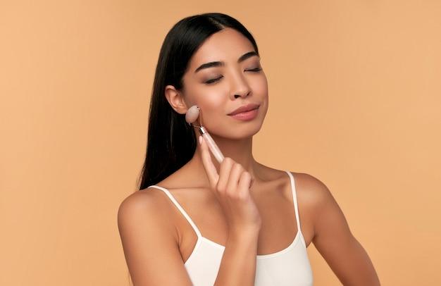 Een jonge aziatische vrouw met een schone stralende huid maakt een gezichtsmassage met een kwartsroller op beige