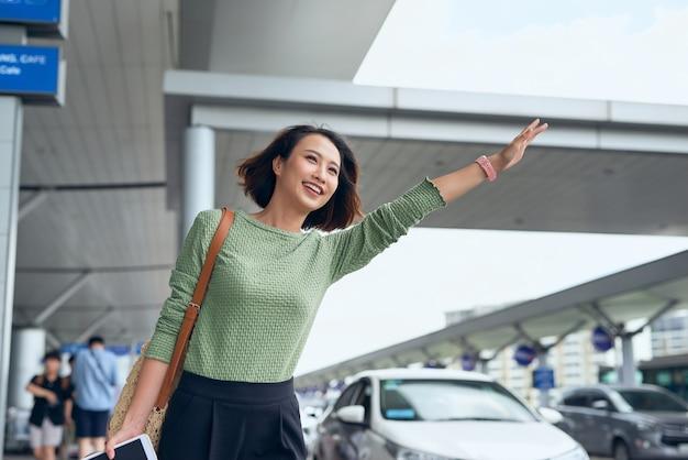 Een jonge aziatische vrouw ziet haar auto die ze heeft geboekt via een app voor ritjes en zwaait ermee