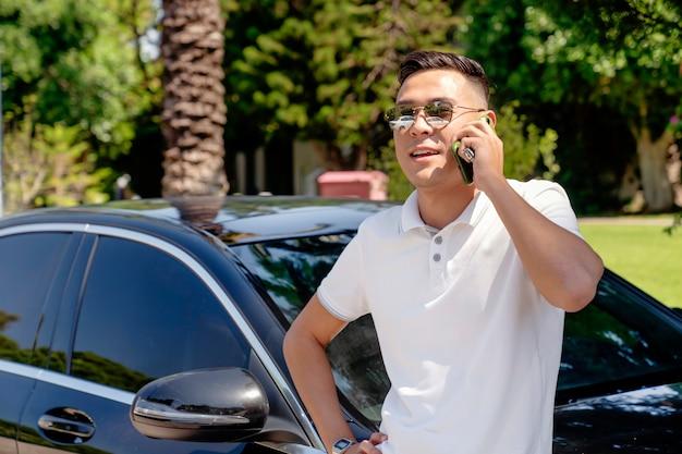 Een jonge aziatische zakenman, een man in een wit overhemd en zonnebril, staat in de buurt van een moderne auto en praat op een mobiele telefoon, lost problemen en vragen op, glimlacht.