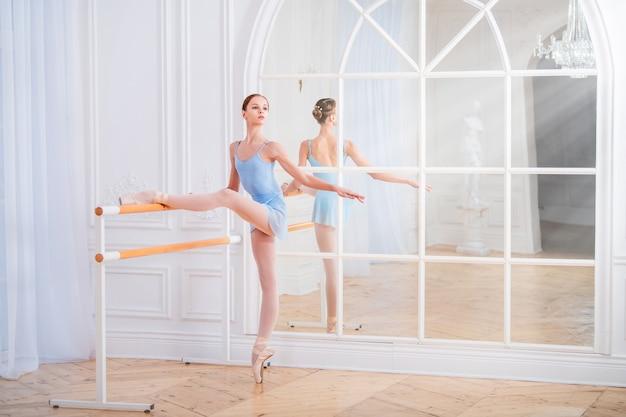 Een jonge ballerina houdt zich bezig met klassiek ballet bij de machine in een mooie witte zaal tegen de spiegel.
