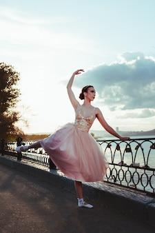 Een jonge ballerina in een roze zijden jurk danst en voert oefeningen uit die zich vasthouden aan een gietijzeren hek...