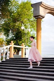 Een jonge ballerina in een roze zijden jurk loopt sierlijk de trap af in een boog met zuilen op de... Premium Foto