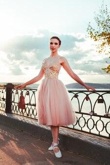 Een jonge balletdanser staat in een roze jurk en tsjechen met linten op een gietijzeren balustrade van de ri...