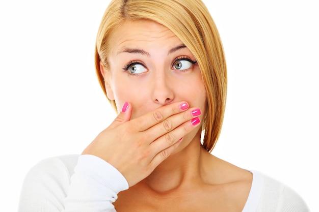 Een jonge bange vrouw die haar lippen bedekt met handen op een witte achtergrond